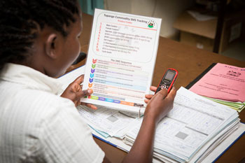 In Nairobi, Kenya, a facility in-charge uses her phone and a system job aid to submit a monthly CDRR (consumption data report and request form) to the Tupange SMS commodity tracking system (TSCTS).